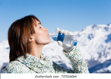 woman drinking mineral water in snow
