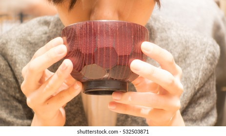 A woman drinking miso soup