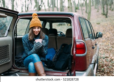 Woman drinking in off rad car in forest