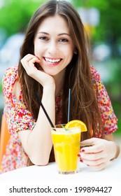 Woman drinking orange cocktail