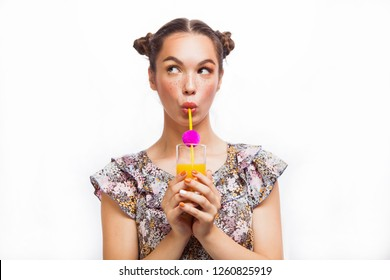 Woman drinking orange juice smiling happy excited. Beauty Teenager Model Girl. Beautiful Joyful teen girl with freckles and yellow makeup. Professional make up.