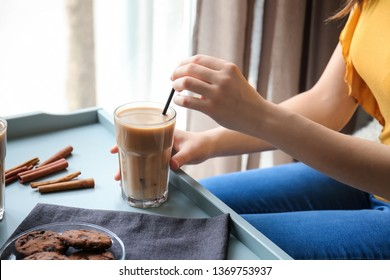 Woman drinking tasty frappe coffee at home