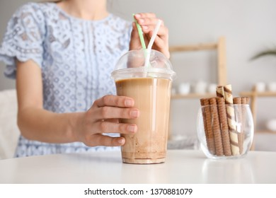 Woman drinking tasty frappe coffee at table