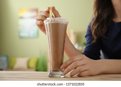 Woman drinking tasty frappe coffee at wooden table