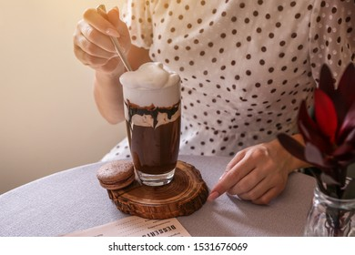 Woman drinking tasty frappe coffee in cafe
