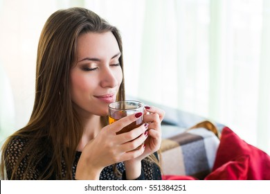 woman drinking tea at home. enjoying its taste and aroma