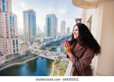 woman drinking tea in a luxury apartment with the cityscape view in dubai, UAE
