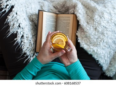 A woman is drinking tea and reading a book, female hands are holding a glass beaker with a drink. Lifestyle, relaxation.