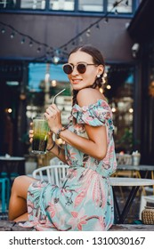 Woman drinking vegetable smoothie after fitness running workout on summer day. Fitness and healthy lifestyle concept, outdoor close up portrait, hipster, juice, tasty, sweet, sunglasses