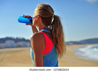 Woman drinking water after running on beach