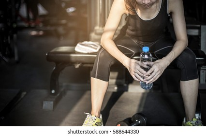 Woman drinking water after training in gym .Young woman sitting at gym after her workout. Female athlete taking rest after exercising at gym.