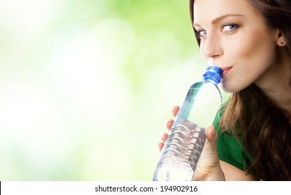 Woman drinking water from bottle, outdoors, with blank area for copyspace