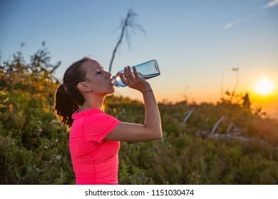 Woman drinking water from water bottle. Woman trail runner. Szczyrk, Beskidy Mountains, Poland