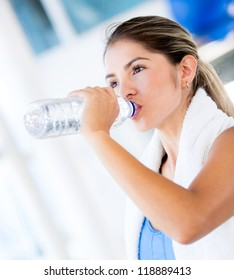 Woman drinking water at the gym after working out