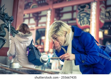 woman drinking water to the holy fountain in Asakusa temple, Tokyo