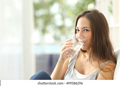 Woman drinking water at home and looking at you sitting on a couch in the living room at home