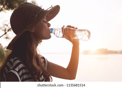 Woman drinking water in summer morning sun