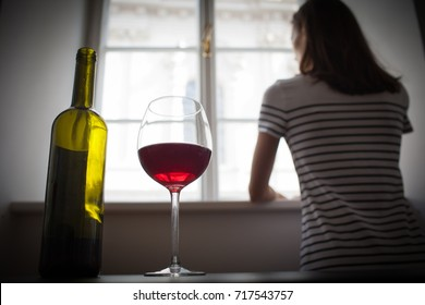 Woman drinking wine alcohol alone looking out her window.  Depression, alcoholism, lonely person concept.
