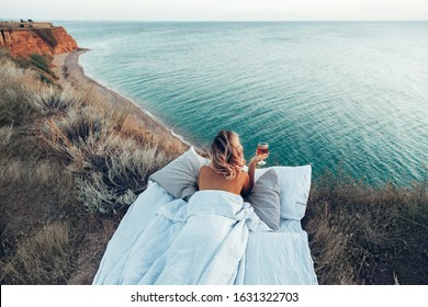 Woman drinking wine enjoying view on beach landscape while relaxing in bed on mountain in sunset on the edge of Earth. Calm and quiet wanderlust concept moment when person feels happiness and freedom.