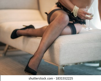 woman drinking wine on chaise lounge in hotel wearing garter with nylon stockings and high heels and pearls on her wrist