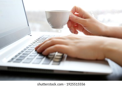 Woman drinks coffee sitting at laptop keyboard on window background. White cup of hot drink in female hand in sunshine, good morning, break during work