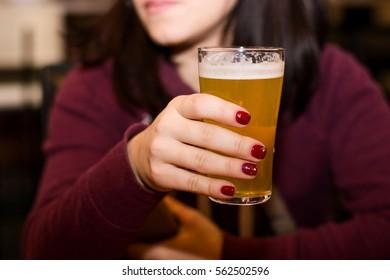 Woman drinks fresh beer in cafe