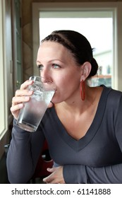 Woman drinks glass of ice water