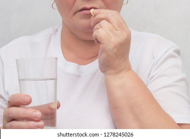 A woman drinks a hormonal pill for treating the thyroid gland, eliminating nodules and normalizing hormones, treatment, close-up