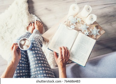 Woman drinks hot chocolate and reads a book in cozy home atmosphere