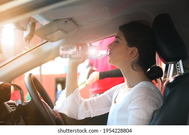 woman drinks Water in the Car, Thirsty Behind the Wheel , Woman driver drinks water from a refillable bottle in her car, thirsty behind the wheel, stopped to rest.