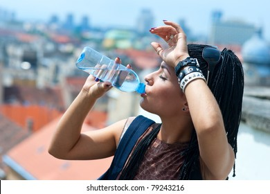 woman drinks water from plastic bottle