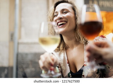 A woman drinks white wine at a table in an outdoor cafe with friends. Adults aged forty years experience moments of relaxation and fun together with an aperitif.
