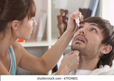 Woman dripping man eye with eyes drops