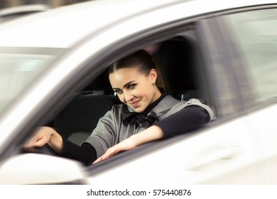 Woman driver. Beautiful blue eyed woman sitting in her car smiling.