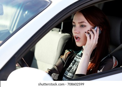 Woman driver in a car. Young lady in an automobile looks very upset or scared of something