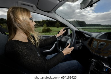 Woman driver driving car on country road
