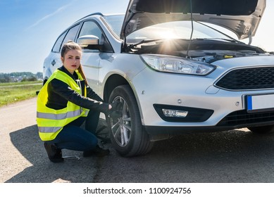 Woman driver going to change damaged wheel