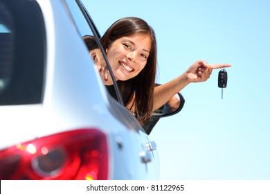 Woman driver holding car keys driving her new car. Beautiful multiracial young woman.