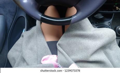 Woman driver legs inside car in gray fashionable coat
