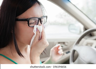 Woman driver sneezing in the car. Sick woman driver.