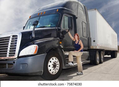Woman driver at the wheel of her commercial 18-wheeler diesel semi truck.