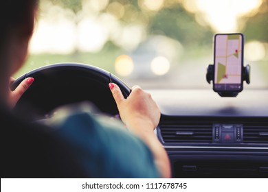 A woman drives a car at sunset