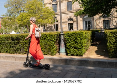 Woman drives electric scooter in the city