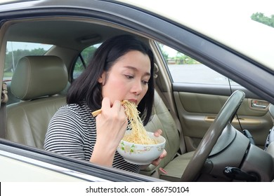 woman driving car and eating noodle