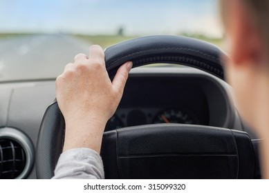 Woman driving car, hand on steering wheel, looking at the road ahead, road safety, selective focus on hand with shallow depth of field.