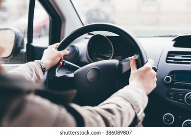 Woman driving car. Hands on the steering wheel.