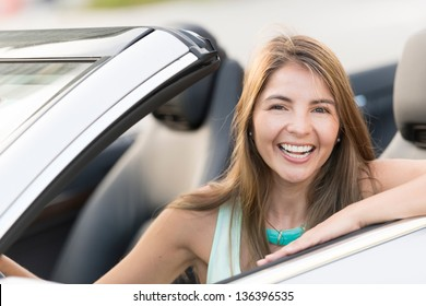 Woman driving a car looking very happy and smiling
