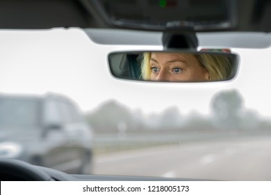 Woman driving a car on a highway on a misty day with her eyes white opened reflected in the mirror