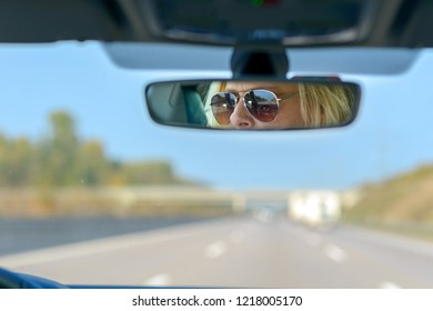 Woman driving a car on a motorway with a view ahead through the windscreen and her glasses reflected in the rear view mirror