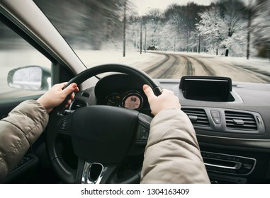 Woman driving the car on snowy road